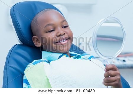 Smiling young boy looking at mirror in the dentists chair