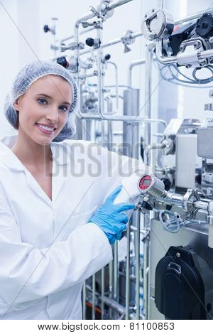 Smiling scientist leaning against gauge in the factory