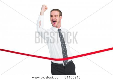 Businessman crossing the finish line while clenching fist on white background