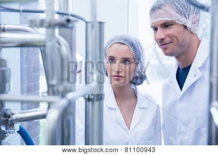 Smiling scientist with colleague looking metal gauge in the factory