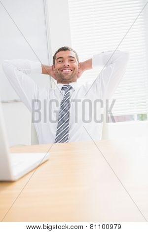 Businessman relaxing in a swivel chair leaning ahead