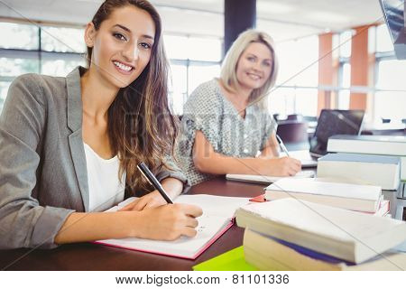 Smiling matures females students writing notes at desk in library