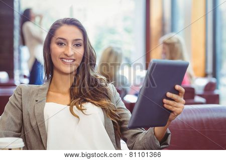 Student using digital tablet and holding disposable cup in library