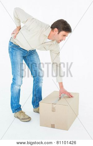 Full length of delivery man with cardboard box suffering from backache on white background
