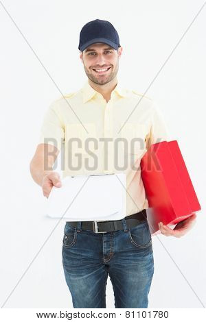 Portrait of happy courier man with red box giving clipboard for signature on white background