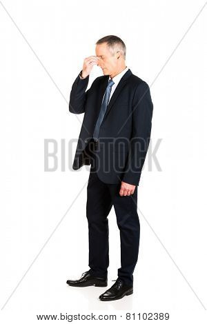 Mature businessman suffering from sinus pressure pain