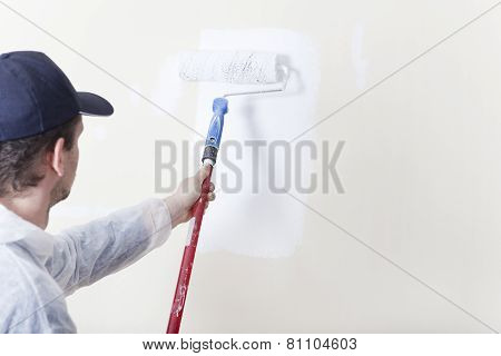 Painter Paints Wall With Paint Roller White