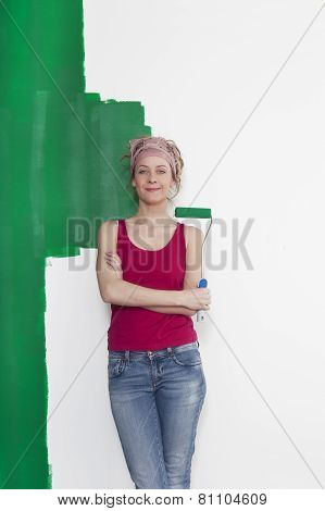 Woman With Paint Roller In Front Of Wall