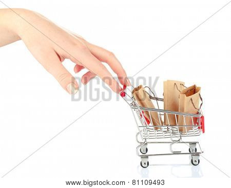Female hand pushing small shopping cart with bags, isolated on white