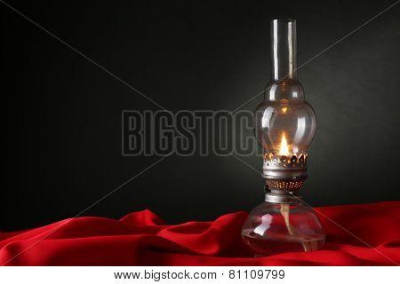 Kerosene lamp on red cloth on dark background