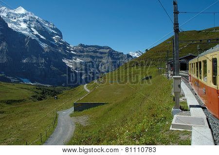 Peaks, Meadow And Train In Kleine Scheidegg In Switzerland