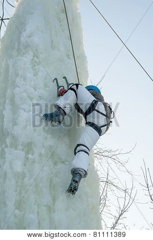 Girl climbs upward on ice climbing competition