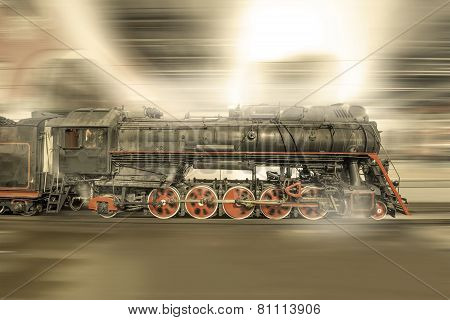 Steam train goes fast on the night station background.