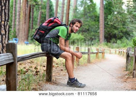 Hiking man portrait with backpack tired resting legs after long hike in nature. Caucasian man smiling happy with forest in background during summer trip in Yosemite National Park, California, USA.