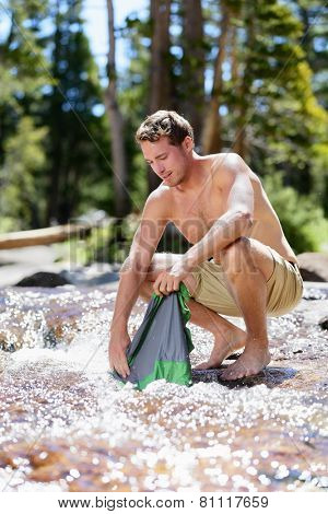 Camping hiking hiker man washing clothes on trek in nature river. Hiking young male adult doing clothing wash chores in natural stream of fresh water during an adventure trip outdoors.