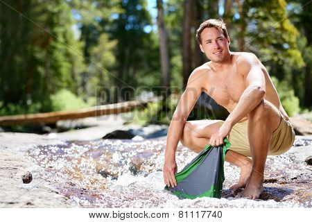 Camping hiker man washing clothes on trek in nature river. Hiking young male adult doing clothing wash chores in natural stream of water during an adventure trip outdoor.