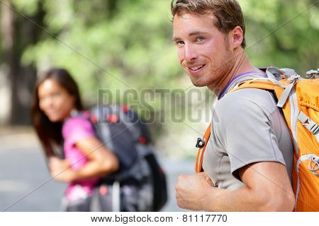 Hiking people. Young couple of hikers walking. Caucasian man smiling happy in foreground with young woman in background during summer trip in Yosemite National Park, California, USA.