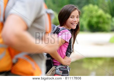 Hiker. Woman hiking smiling happy on trek with backpack during summer outdoors activity. Multiethnic Asian Caucasian female model walking with a group on a day excursion trip hike in the forest.