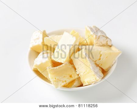 Pieces of French white rind cheese in a bowl