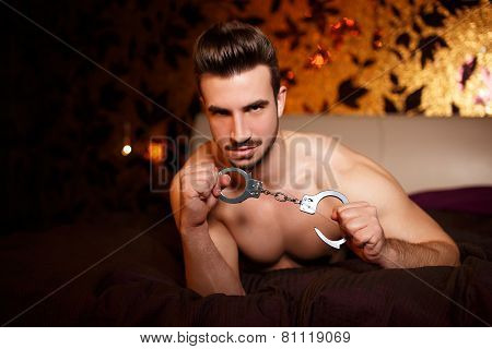 Sexy Macho Man With Handcuffs Laying On Bed