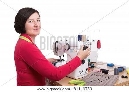 Woman Seamstress At The Sewing Machine. Sews Clothes.