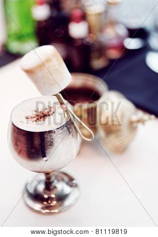 Cocktail with marshmallow in old metal goblet, selective focus, toned
