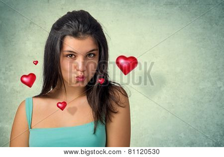 Beautiful brunette teenager expressing a kiss with hovering hearts