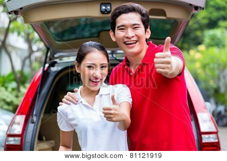 Asian couple loading suitcase for travel in luggage trunk of car