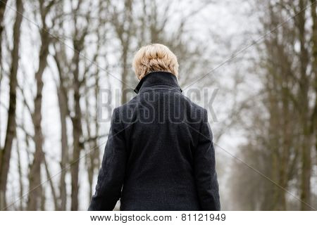 Depressed or sad woman walking down a barren path in winter