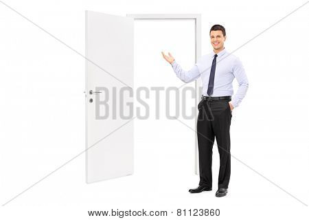 Full length portrait of a young man pointing towards an opened door isolated on white background
