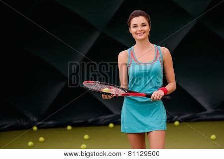 Cheerful woman with racquet and tennis ball