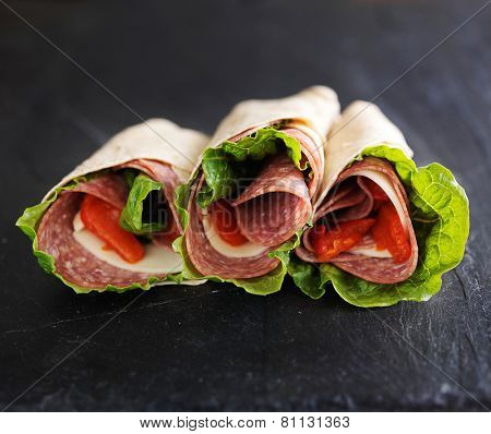 italian wraps with hard salami, lettuce, provolone cheese and roasted pepper
