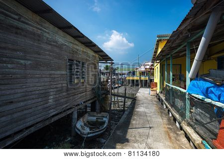 PULAU KETAM, MALAYSIA - JANUARY 18, 2015: A fishermen's boat docks close to his home on stilts in a village on Pulau Ketam (Crab Island). This island is famous for sea food products and restaurants.