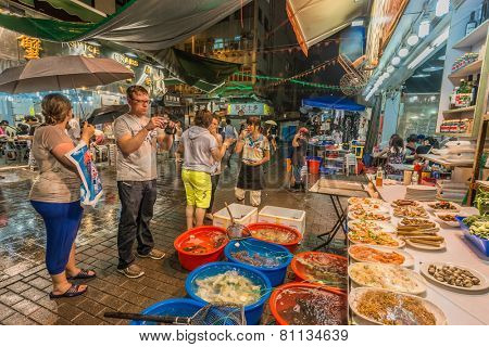Kowloon, Hong Kong, China- June 8, 2014: people outside seafood restaurants in the Temple street night market Tsim Sha Tsui