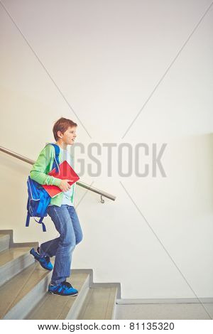 Pre-teen schoolboy with backpack going downstairs