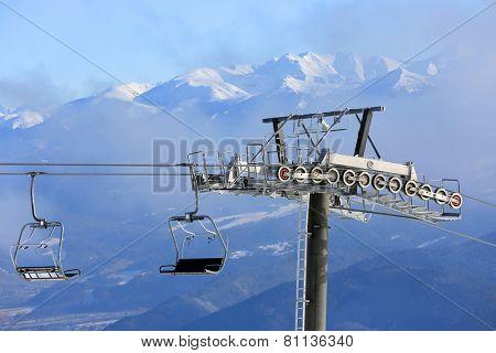 Chairlift on winter ski resort against mountain background