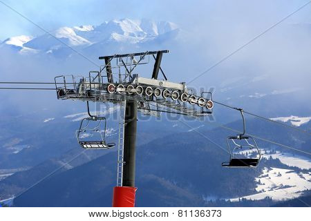 Chairlift on winter ski resort with mountain Background