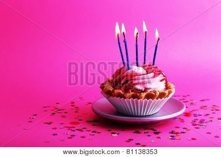 Birthday cup cake with candles and colorful stars on pink background