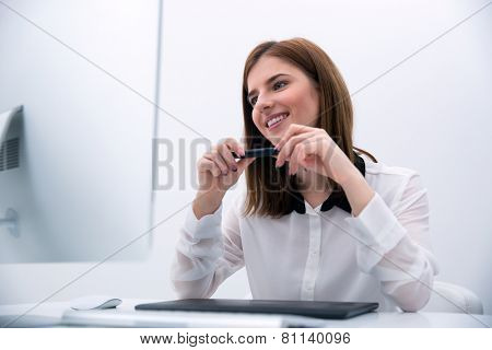 Happy beautiful photo editor working on computer in office