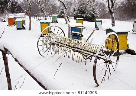 Old  Snowy Horse Drawn Hay Rake And Beehive In Winter Farm Garden