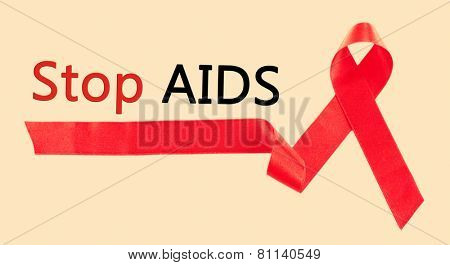 Red AIDS ribbon on beige background