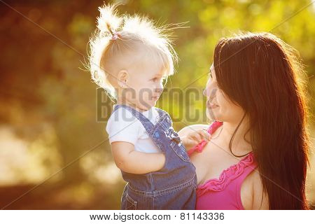 Mother and little daughter play in the summer in the Park.