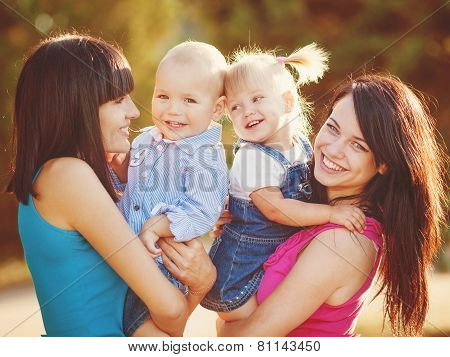 Young mothers and young children in the summer on a walk in the Park.