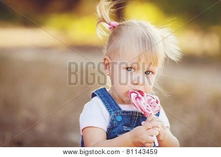 Little girl with lollipop in summer park.