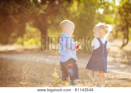 Small children, a boy and a girl, playing in the Park on the grass.