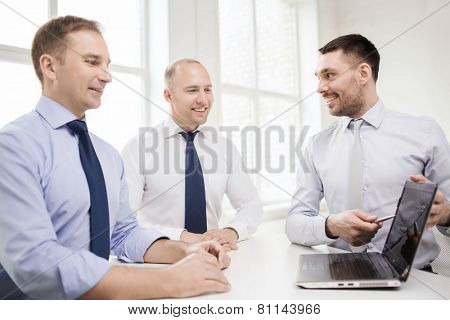 business, technology and office concept - smiling businessmen with laptop computer and papers having discussion in office