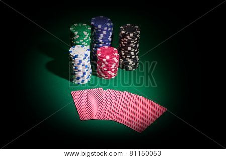 Chips and playing cards on green table