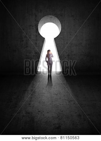 businesswoman against black wall with key hole