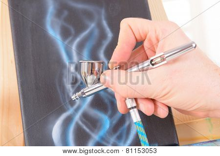 Hand holding a professional airbrush and painting