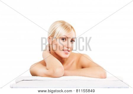 Spa. Face skincare beauty woman smiling happy. Beautiful attractive female model lying down on towel